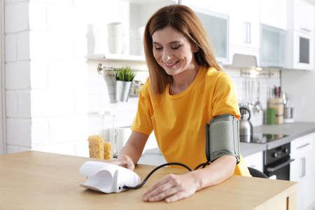 Frau, die den Blutdruck mit Blutdruckmessgerät am Tisch im Haus überprüft. Kardiologie-Konzept
