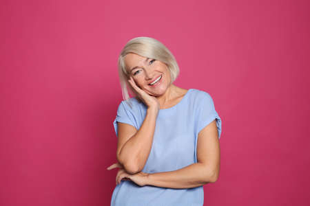 Portrait of mature woman laughing on color background