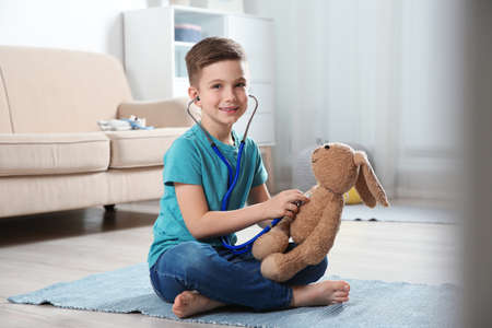 Cute child imagining himself as doctor while playing with stethoscope and toy bunny at home Foto de archivo
