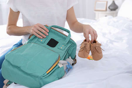 Woman packing baby accessories into maternity backpack on bed, closeup Imagens