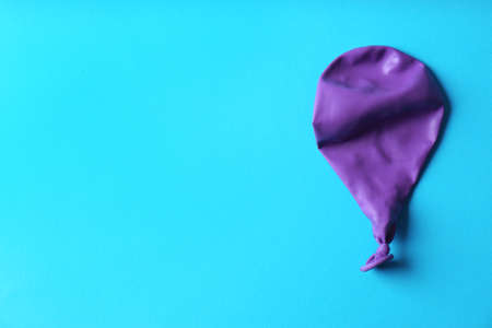 Purple deflated balloon on color background, top view with space for text