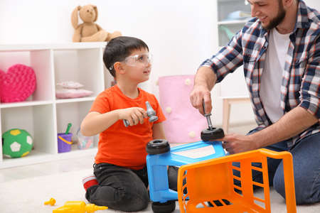 Man and his child as repairman playing with toy cart at home