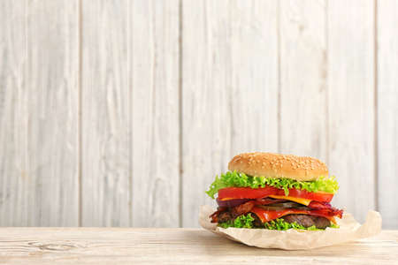 Tasty burger with bacon on table against wooden background. Space for text