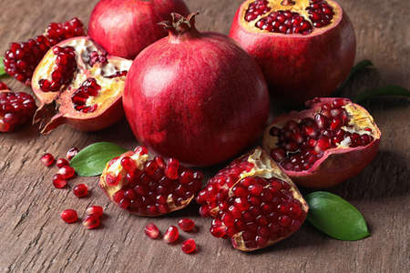 Composition with ripe pomegranates and leaves on color background