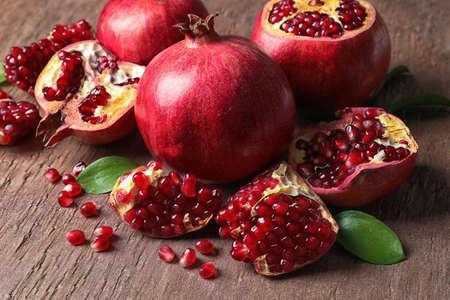 Komposition mit reifen Granatäpfeln und Blättern auf farbigem Hintergrund Standard-Bild