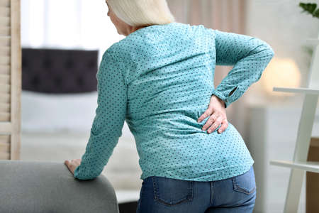 Senior woman suffering from back pain at home 版權商用圖片