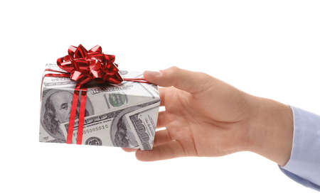 Man holding gift box wrapped in decorative paper with dollar pattern on white background, closeup Stock Photo