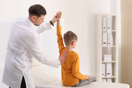 Chiropractor examining child with back pain in clinic