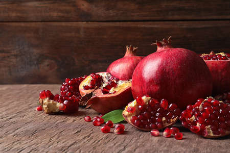 Composition with ripe pomegranates and leaves on table. Space for text