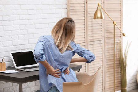 Young woman suffering from back pain in office Reklamní fotografie