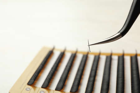 Tweezers with artificial eyelash on blurred background, closeup. Space for text