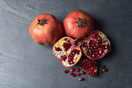 Ripe juicy pomegranates on grey background, top view