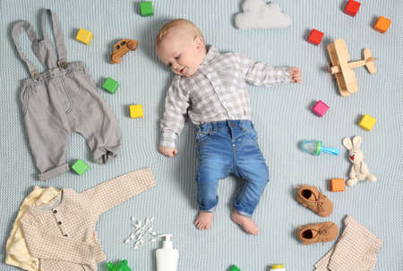 Cute little baby with clothing and accessories on color blanket, top view 写真素材