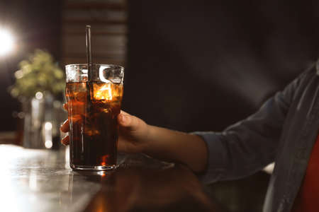 Woman with glass of refreshing cola at bar counter, closeup