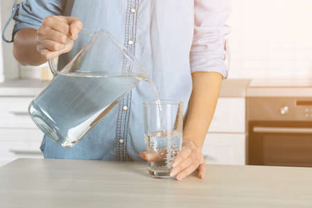 Woman pouring water into glass in kitchen, closeup. Refreshing drink Stockfoto