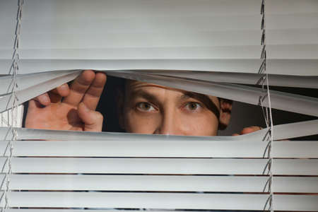 Curious man looking through Venetian window blinds