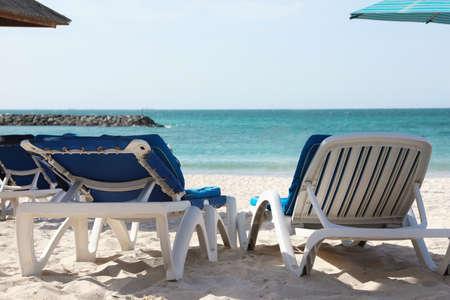 Comfortable sunbeds on sandy beach at tropical resort