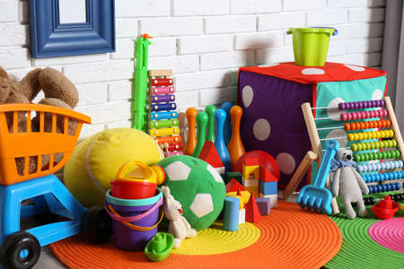 Different child toys on floor against brick wall