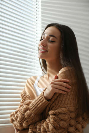 Young woman near window with Venetian blinds
