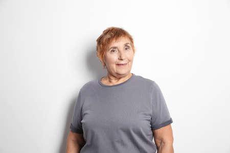 Portrait of elderly woman on light background