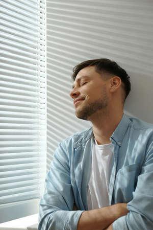 Handsome man near window with Venetian blinds Reklamní fotografie