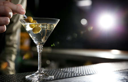 Barman adding olives to martini cocktail on counter, closeup. Space for text Stockfoto