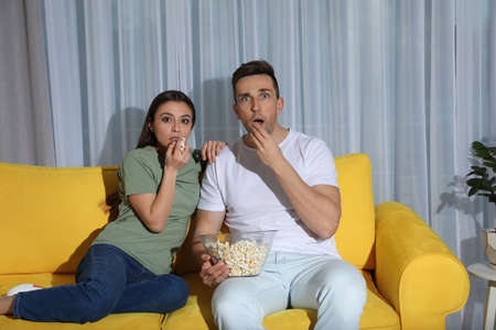 Couple with popcorn watching TV together on couch in living room