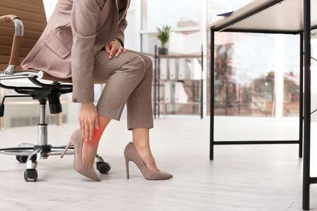 Vrouw die lijdt aan pijn in de benen op kantoor, close-up met ruimte voor tekst