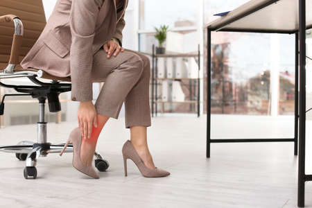 Woman suffering from leg pain in office, closeup with space for text