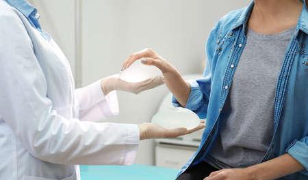 Doctor mostrando implantes de silicona para aumento al paciente en clínica, primer plano. Cirugía cosmética