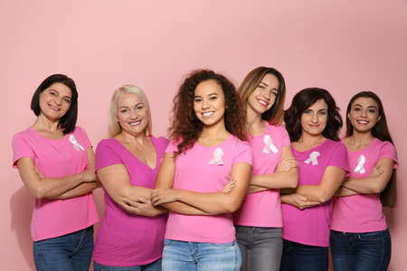 Group of women with silk ribbons on color background. Breast cancer awareness concept