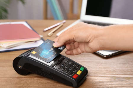 Woman using terminal for contactless payment with credit card at table
