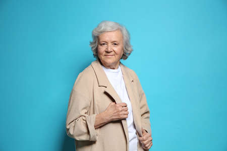 Portrait of elderly woman on color background Imagens