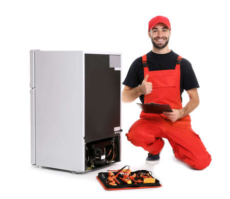 Male technician with clipboard and tools near broken refrigerator on white background