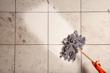 Limpiador profesional que lava el piso sucio con un trapeador, vista superior. Espacio para texto