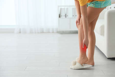 Woman suffering from leg pain at home, closeup. Space for text