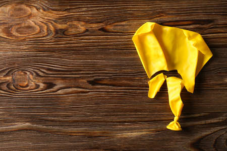 Popped yellow balloon on wooden background, top view with space for text Stock Photo