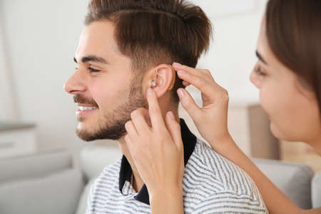 Woman putting hearing aid in man's ear indoors