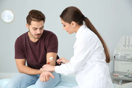 Female doctor cleaning young man's arm injury in clinic. First aid Banque d'images - 117357846