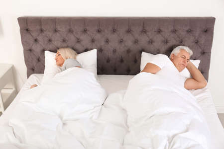Mature couple sleeping back to back in bed at home. Relationship problems