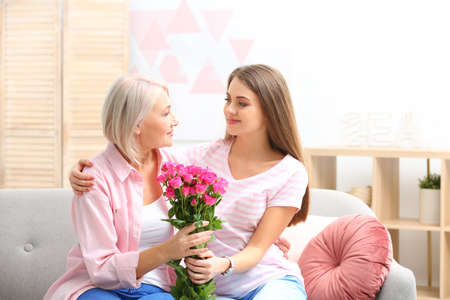 Young daughter congratulating her mature mother at home. Happy Womens Day