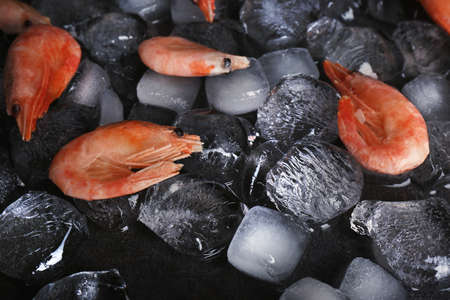 Shrimps and ice cubes on table, closeup 免版税图像