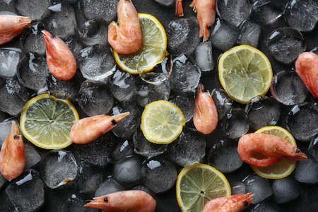 Flat lay composition with shrimps, lemon slices and ice cubes on dark background