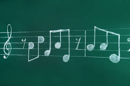 Music staff with treble clef and notes written on chalkboard
