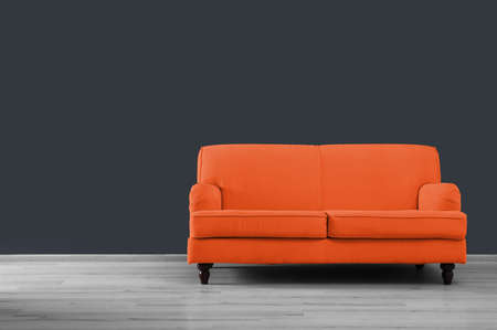 Stylish orange sofa in room near grey wall. Space for text Reklamní fotografie
