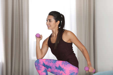 Young woman in fitness clothes doing exercise with dumbbells at home