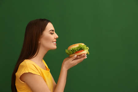 Young woman eating tasty burger on color background. Space for text