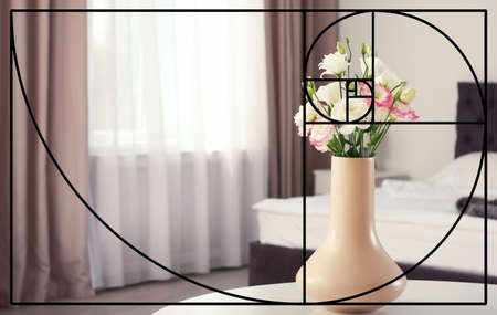 Fibonacci spiral and vase with flowers on table in bedroom. Golden ratio concept