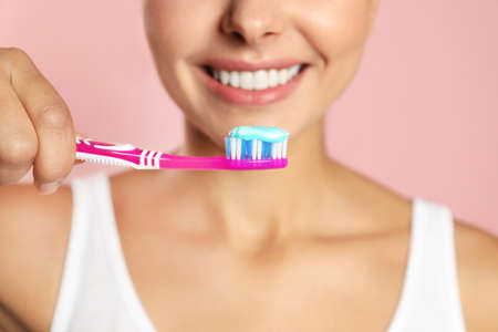 Young woman with toothbrush and paste on color background, closeup. Teeth care Imagens
