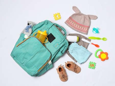 Komposition mit Umstandsrucksack und Babyzubehör auf weißem Hintergrund, Ansicht von oben
